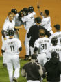 The Rockies players mob Garrett Atkins after his game-winning hit in the 9th inning of the...
