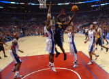 Denver Nuggets forward Reggie Evans goes up for a shot against Los Angeles Clippers' defenders...