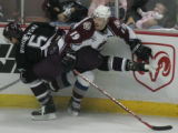 JPM428   The Mighty Ducks of Anaheim Vitaly Vishnevski traps Colorado Avalanche Joe Sakic against...