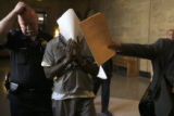 Michael Asberry (cq) covers his face after appearing in Denver District Court on Wednesday April...