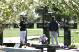 Visitors place flowers on the memorials of the Columbine victims at the Chapel Hill Cemetery in...