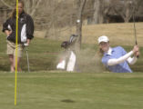 Jenna Zamprelli, left, watches as Becca Huffer, right, hits out of the sand toward the pin near...