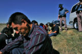 Illegal immigrant Heliodoro San Aguston Velasco, cq, left, waits with 16 other co-riders on the...