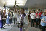 Pastor Peter Moriin (cq) waves a palm leaf to lead his congregation into worship during Palm...