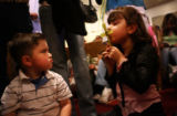 Orlando Espino, 2, makes a face as his cousin Miraiah Stettler-Amaro kisses a cross made out of a...