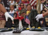 Members of the National Honor Guard prepare to turn glasses upside down during a ceremony for...