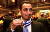 (DENVER, Colo., January 13, 2005) Matt Casias holds up his medal of valor that Gov. Bill Owens...