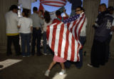 Ely Pinedo,4, (cq), plays under a flag draped over her mothers shoulders, Rocio Aguayo, (cq), as...