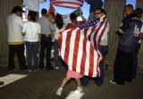 Ely Pinedo (cq), 4, plays under a flag draped over the shoulders of her mother, Rocio Aguayo (cq),...