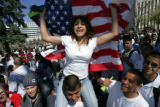 Eva Lopez (cq), 15, waves a U.S. flag while sitting on the shoulders of Jorge Gonzalez (cq), 15,...