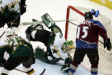 The Colorado Avalanche's Andrew Brunette (#15) puts the puck past a diving Dallas Stars' Marty...