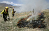 (L-R) Carol Von Michaelis (cq) with Genesee Fire lays down a fire with drip pot during a...