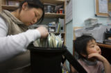 Mun Song, 32, struggles with paperwork and keeping the family store open  with her son Alexander...
