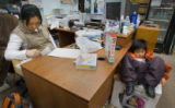 Boredom sets in as Mun Song, 32, left, finishes up for the day while her son Alexander Min, 7,...