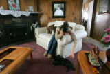 Alejandra, 17, plays with her dog in her front-room where a portrait of her in her quinceanera...