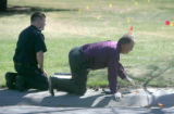 Aurora crime scene investigators R.J. Wilson (CQ), left, and Harrel (cq), right, examine peices of...
