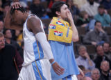 Denver Nuggets forward Carmelo Anthony, left, leaves the floor after fouling out of the ball game...