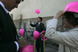 Mayor John Hickenlooper (cq) throws a pink hard hat up to catch on his head while his wife Helen...