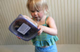 Two-year-old Daisy Nyman (cq) tries to open a frozen meal from one of the members of her parents...