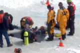 Divers from the Summit County Rescue Group rest on the three foot thick  ice at Dillon Reservoir...