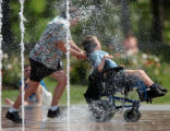 {DENVER, COLO., JUNE 8, 2004}--  Steve Rider and his son, Gordon Rider, 11, cool off from the heat...
