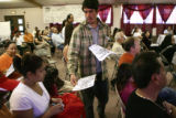 Eugenio Rodarte (cq), of Denver, hands out fliers at a public meeting hosted by the radio station...
