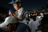 Imanol Flores, 4, rides on his father Juan Flores's, 28, of Denver, CQ, shoulders as thousands of...