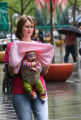 April Richardson (cq) protects her 3-month-old baby girl Taylor Richardson from a rain shower with...