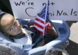 "Axel Sanchez (cq), 1, of Aurora, sits in his stroller with a sign that says ""We're not..."