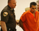 A Weld County Deputy Sheriff hand-cuffs Damion Campos and escorts him back to jail after appearing...