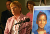 Arapahoe County D.A. Carol Chambers stands next to a picture of Aarone Thompson (accent over e) at...