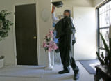 Broderick Bell (cq), 19, puts on his graduation cap and gown in his Aurora home before leaving to...