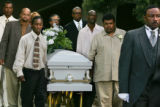 Raphael Lowe, front left, and Aaron Thompson, right,  lead the pallbearers in carrying the casket...
