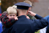 Shane Bishop, cq, 2, hugs his father, Denver Police officer Jack Bishop while he salutes during...