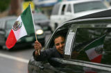 Nestor Navarro holds a Mexican flag out the window of a stretch limo near Federal and 38th to...