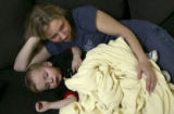 (FOUNTAIN, Colo., March 11, 2005)  Melissa Givens, 28, lies on the couch with her youngest son...