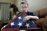 Tanner Segura, 8 holds holds a flag donated to him, and badge of his father, Donnie Young as he...