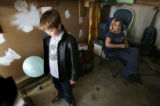 (FOUNTAIN, Colo., March 11, 2005)  Dakota Givens, 7, holds a balloon for his father while his...