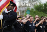 Denver Police Officer Keith Spooner, cq, presents the colors at the start of a ceremony honoring...