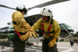 Monument Helitack crew member (lt-rt) Scott Bogges, cq, has his gear safety checked by crew member...