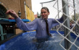 DPS superintendent Michael Bennet spits out water after getting dunked into a 400-gallon tank of...