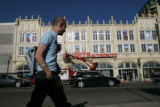Zach Scruggs (cq) of Denver walks past the Sports Castle on his way home as the old  Gart Sports...