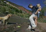 Ryan Rambo (cq), 8,middle, and  Chelsea Bennett, right,  (cq), 13,  play with Bennett's dog Zion,...