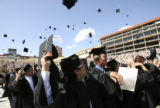 (CENTER FOREGROUND) Business majors Tarun Bhasin, 22, of Boulder, throws his cap in the air at the...