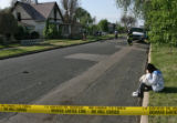 Chantel Gutierrez, granddaughter of home owner Susan Gutierrez, sits on the curb near her...