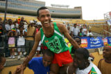 Ethiopian runner Berhanu Adane (#24) is hoisted onto the shoulders of Ethiopian race fans after...
