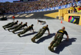 Naval ROTC officer students do 10 Marine Corp pushups before finishing their run at Folsom Field...
