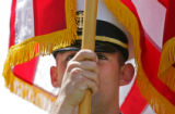 Naval ROTC Color Guard member MIDN Brian Sima (cq), 20, stands at attention with the flag during...