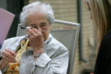 Caroline Vizzi, CQ, 91, left, wipes away tears that came with a rose bush that her daughter, Carol...
