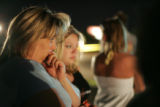 Kathleen Hulme, cq, left, and her daughter, Alexis, cq, 17, watch the scene of a fatal automobile...